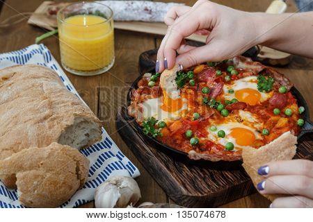 Hand dip bread into flamenco eggs or huevos a la flamenca, spanish andalusian cuisine.