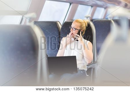 Businesswoman traveling by train, yawning while talking on cellphone and working on laptop. Long and tiresome business travel concept.