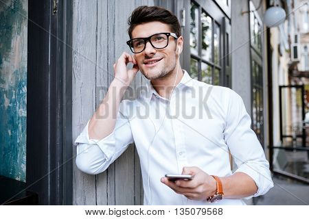 Smiling young man in white shirt and glasses walking and listening to music from smartphone