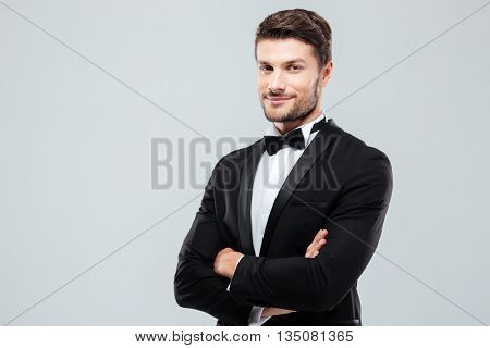 Smiling confident young man in tuxedo standing with arms crossed over white background
