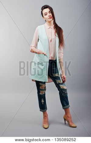 Full-length Portrait Young Brunette Girl Wearing In Pink Blouse, Turquoise Jacket, Ripped Jeans And