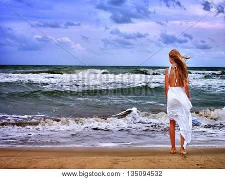 Summer girl sea. Girl goes next to wave on beach . Back view of girl on beach looking at wave.