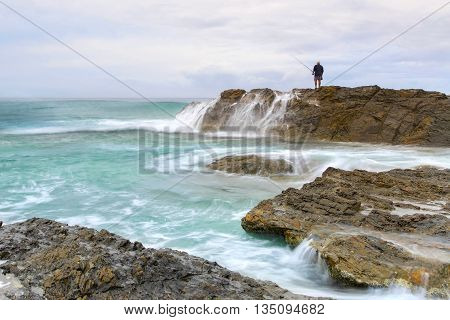 Fisherman fishing from a rock at Currumbin Rock Gold Coast with large ocean swell