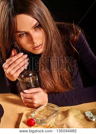 Girl in depression drinking alcohol in solitude. Drinking alcohol habits. Girl is heavy alcohol drinkers. poster