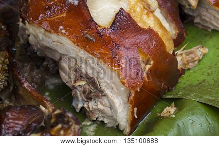 Piece of roasted pork on green banana leaf, pork barbecue cut, whole pig roasted
