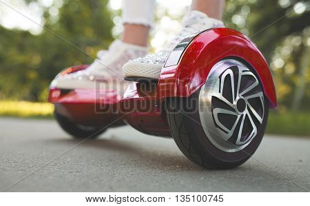 Feet of a girl  riding on modern electric mini segway or hover board scooter. Trending new transport, fun and easy to ride,produces no air pollution to the atmosphere.