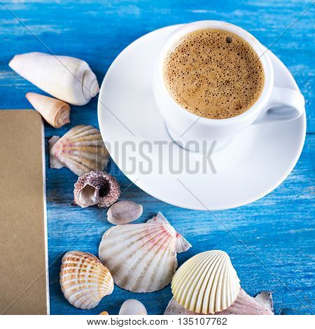 cup of coffee shells mobile phone on the old blue wooden boards sea style. marine still life