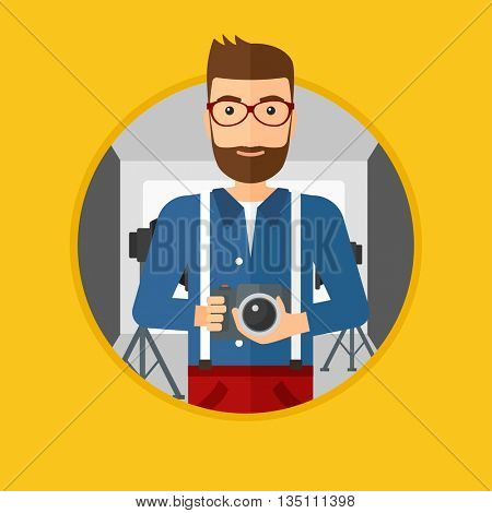 A hipster photographer with the beard holding a camera in photo studio. Photographer using professional camera in the studio. Vector flat design illustration in the circle isolated on background.