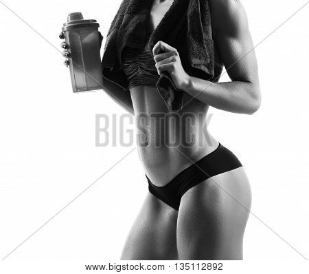 Goals motivation. Monochrome closeup of a sports woman wearing training gear posing with a towel around her neck holding a bottle of water