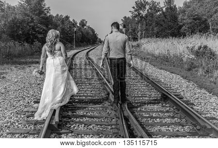 Newlywed couple walking on the rails of a pair of railroad tracks in black and white.