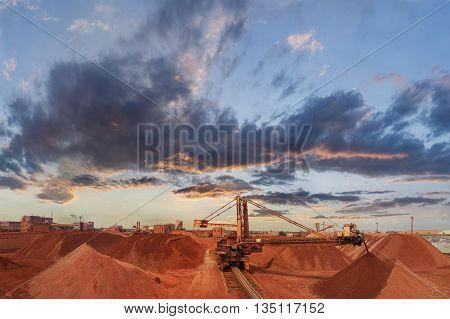 Bucket-wheel excavator load ore. Bauxite ore plot. Conveyer belt machine.