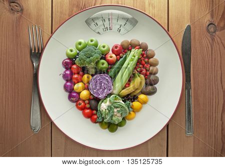 Plate with weighing scales packed with diet fruits and vegtables in a heart shape
