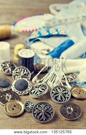 Round metal buttons on a background tailoring accessories. Selective focus.