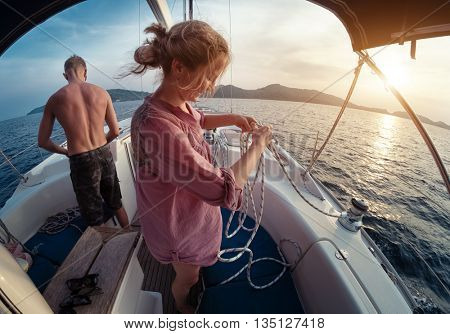 Young lady and man working with winch and ropes on the sailing boat at sunset