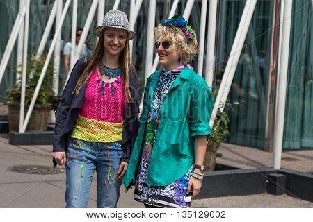 MILAN ITALY - JUNE 18: Two fashionable women pose outside Jil Sander fashion show building for Milan Men's Fashion Week on JUNE 18 2016 in Milan.