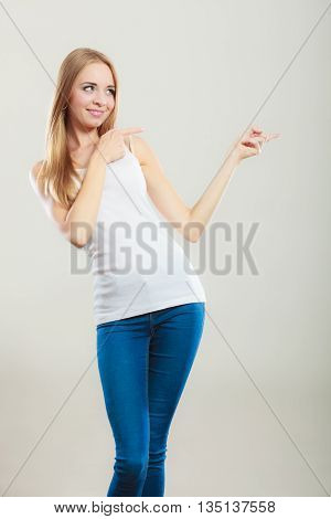 Concept girl advertisement product. Young woman casual style point finger showing something to side empty copy space.