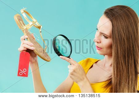 Good shopping summer sale concept. Fashionable woman choosing shoes searching through magnifying glass discount red label with percent sign in hand