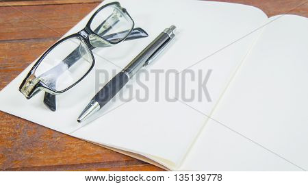open notebook with pen and glasses on a wooden background