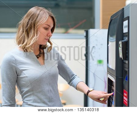Pretty young woman using coffee vending machine.