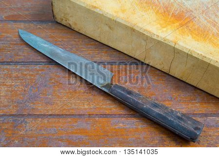 cutting board with a knife on wooden background