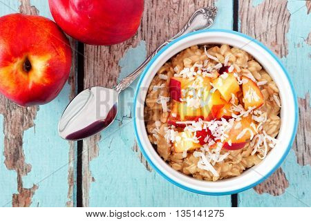 Bowl Of Overnight Breakfast Oats With Diced Peach And Coconut, Overhead Scene On Rustic Wood