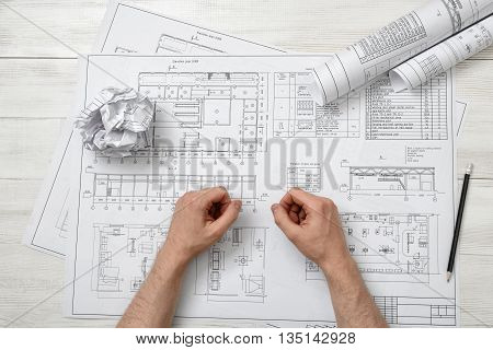 Close-up hands of architect working with a drawing. Workplace of architect. Engineering work. Construction and architecture. Architect drawing. Non-stop work.