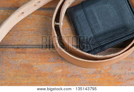 male objects. leather belt and the wallet on wooden background