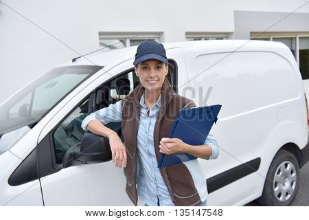 Delivery woman standing by van