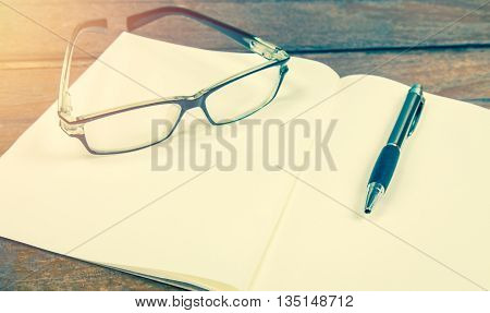 open notebook with pen and glasses on a wooden background (vintage filter)