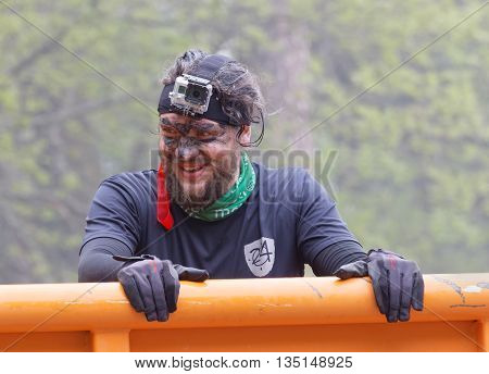 STOCKHOLM SWEDEN - MAY 14 2016: Smling man with mud in his face climbing a orage container obstacle in the obstacle race Tough Viking Event in Sweden May 14 2016