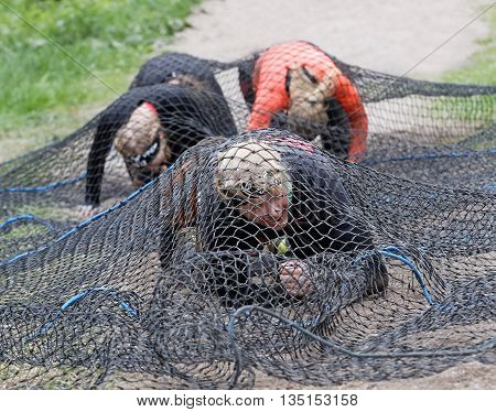 STOCKHOLM SWEDEN - MAY 14 2016: Group of smiling women crawl under a net obstacle in the obstacle race Tough Viking Event in Sweden May 14 2016