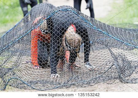 STOCKHOLM SWEDEN - MAY 14 2016: Group of women crawl under a net obstacle in the obstacle race Tough Viking Event in Sweden May 14 2016