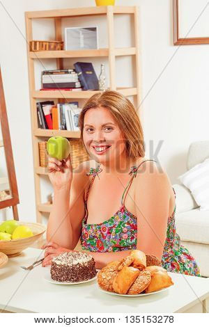 Portrait of fat woman sitting at table full of healthy and unhealthy dishes and foods. Smiling lady holding green apple at home.