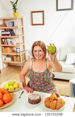 Portrait of fat woman sitting at table and showing green apple to camera at home. Beautiful red haired lady smiling.