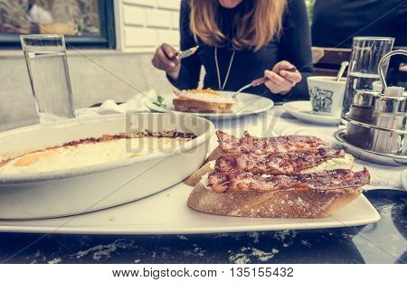 Young woman eating breakfast. Delicious fried bacon on crunchy toast with eggs from the oven.