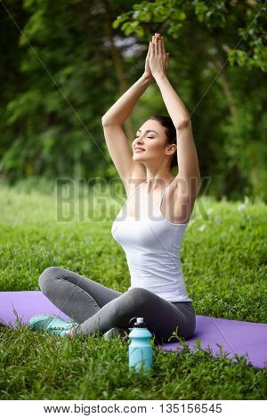 Happy young girl is doing yoga in the nature. She is raising her arms while joining palms. Lady is sitting on lotus position and smiling