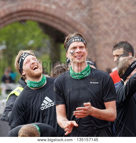 STOCKHOLM SWEDEN - MAY 14 2016: Two men laughing before sprinting towards the rampage obstacle in the obstacle race Tough Viking Event in Sweden May 14 2016