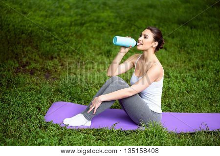 Healthy girl is drinking water after training. She is sitting on fitness mat on grass and smiling