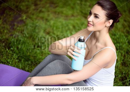 Joyful young woman is relaxing after exercising. She is holding a bottle of water. Athlete is sitting on grass and smiling