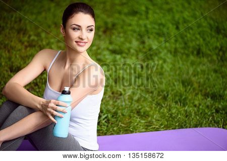 Beautiful girl is drinking water after yoga. She is sitting in the nature and smiling. Copy space in right side