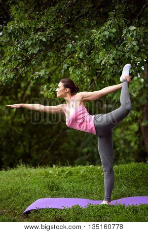 Beautiful fit girl is exercising in the park. She is raising her leg up while stretching arm forward. Athlete is standing and smiling