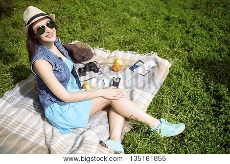 Pretty young woman is enjoying the nature. She is sitting on blanket and laughing