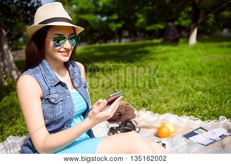 Joyful girl is using mobile phone and smiling. She is sitting on blanket in park and relaxing