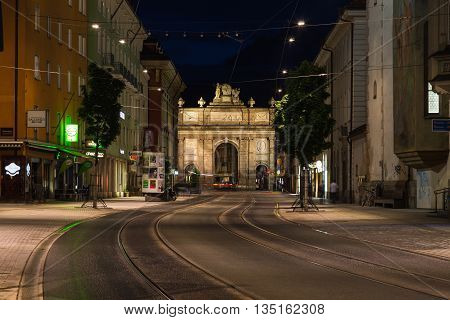 INNSBRUCK AUSTRIA - 18TH JUNE 2016: A view along Maria Theresien Strasse towards Triumphpforte (Triumphal Arch) in Innsbruck at night