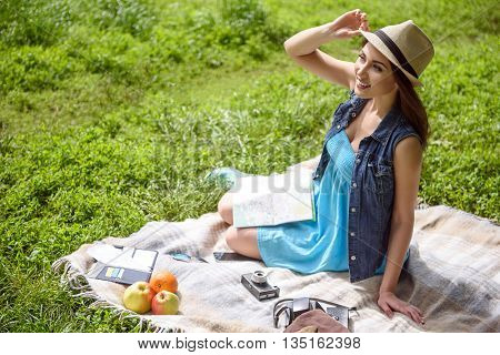 Curious female tourist is relaxing in the nature. She is sitting on blanket on grass and smiling. Woman is looking forward with interest