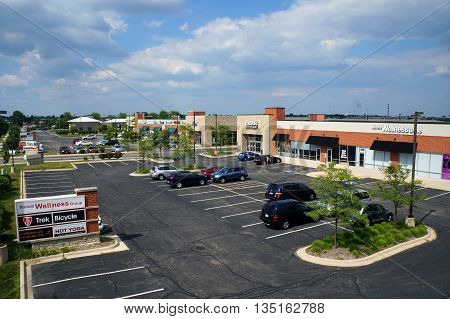NAPERVILLE, ILLINOIS / UNITED STATES - JULY 23, 2015: A Naperville strip mall includes the Illinois Wellness Group, Trek Bicycle, the Naperville Running Company, and Hot Yoga.