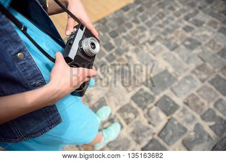 Close up of female hands holding a camera. Woman is standing on street