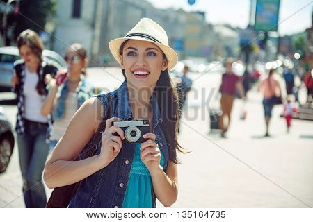 Admired young woman is traveling across city. She is looking forward with interest and photographing. Girl is standing and smiling
