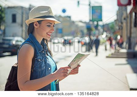 Curious female tourist is reading a map of city. Woman is standing and smiling