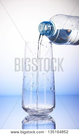 Water Pouring From Plastic Bottle Into Empty Drinking Glass